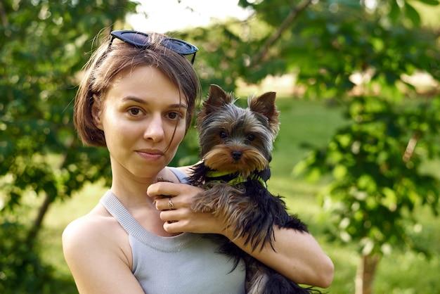 Jolie belle femme avec petit yorkshire terrier dans un parc à l'extérieur. portrait de style de vie