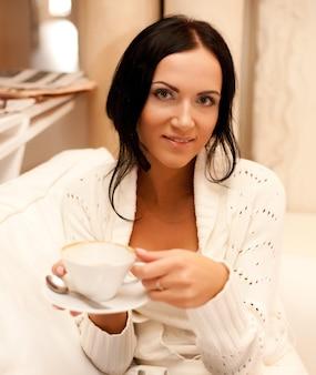 Une jolie belle femme tenant une tasse de café