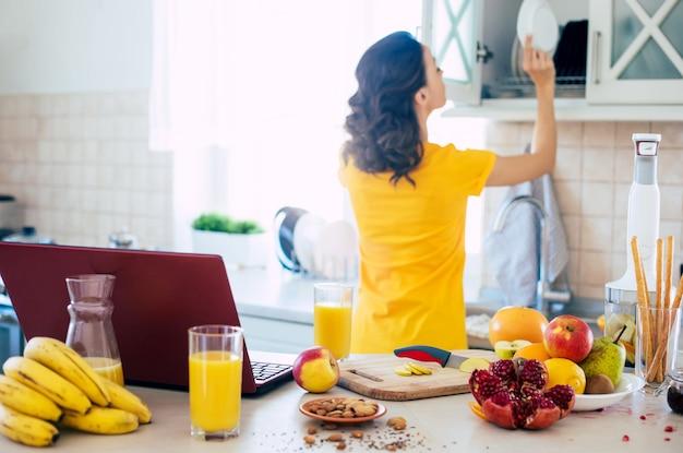 Jolie belle et heureuse jeune femme brune dans la cuisine à la maison prépare une salade de fruits