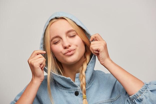 Jolie belle jeune femme blonde avec tresse, les mains gardent le capuchon, envoie un baiser d'air avec les lèvres