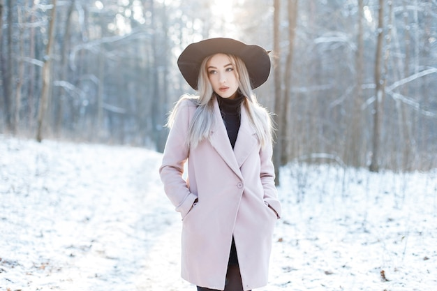 Jolie belle jeune femme dans des vêtements glamour chauds et élégants marche dans un chapeau élégant dans une forêt enneigée par une journée d'hiver ensoleillée. jolie fille moderne à la mode.