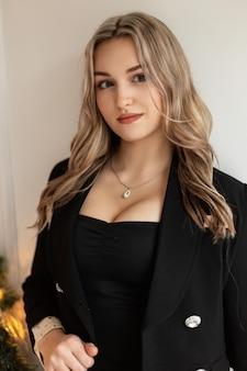 Jolie belle jeune femme vêtue de vêtements noirs à la mode avec un élégant blazer et de gros seins se tient près d'un mur blanc