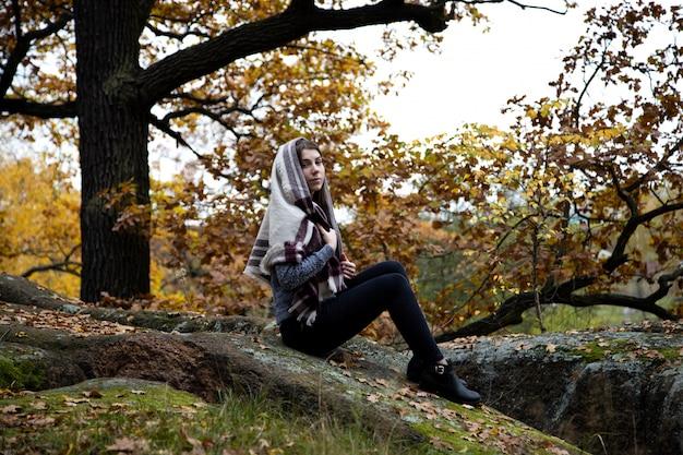Une jolie, belle et modeste fille de religion avec un foulard ou un foulard sur la tête est assise à l'automne dans un parc sur une pierre.