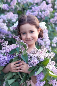Jolie belle petite fille avec lilas en robe rose.