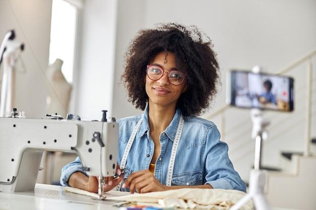 Jolie blogueuse afro-américaine avec des ciseaux et des lunettes sur le lieu de travail dans un atelier de couture