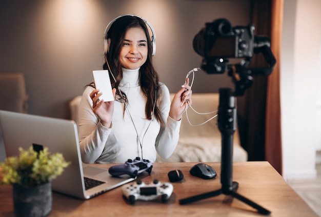 Jolie blogueuse surprise femme dans les écouteurs est en streaming en direct parler de jeux vidéo. influenceur jeune femme en direct streaming hold power bank.