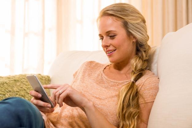 Jolie blonde à l'aide d'un smartphone sur le canapé du salon