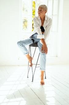 Jolie blonde assise sur la chaise et regardant de côté le mur