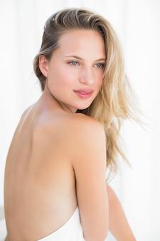 Jolie blonde assise sur une table de massage