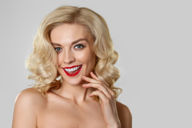 Jolie blonde aux cheveux ondulés, maquillage pour les yeux de chat et les lèvres rouges