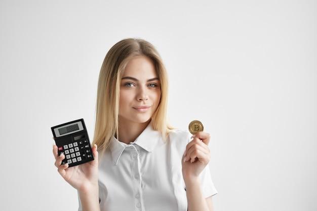 Jolie blonde avec calculatrice pièce d'or crypto-monnaie financière