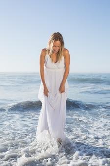 Jolie blonde debout dans la mer sur la plage en robe blanche