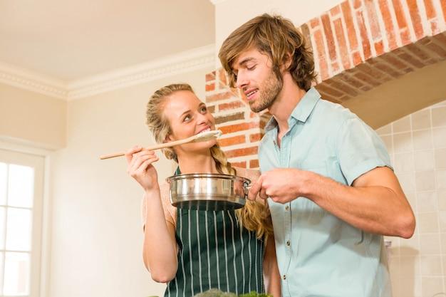 Jolie blonde faisant goûter à son copain la préparation en cuisine