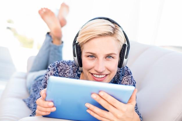 Jolie blonde femme allongée sur le canapé et écoute de la musique