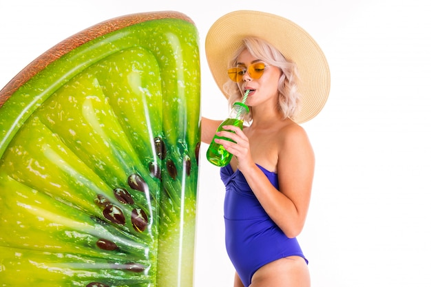 Jolie blonde femme caucasienne se tient en maillot de bain avec matelas de plage en caoutchouc kiwi, boire du jus et des sourires isolé sur fond blanc