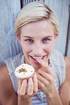 Jolie blonde femme dégustant le cupcake
