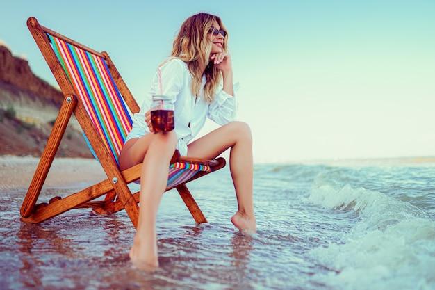 Jolie blonde femme en forme de lunettes de soleil coeur, chemise blanche et maillot de bain dépouillé relaxant sur une plage de transats et boissons cocktail. concept de vacances d'été