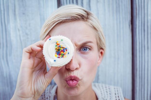 Jolie blonde femme grimaçant avec cupcake