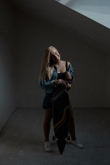 Jolie blonde femme avec longboard dans une pièce sombre