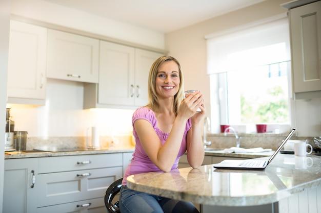 Jolie blonde femme prenant un café et utilisant un ordinateur portable