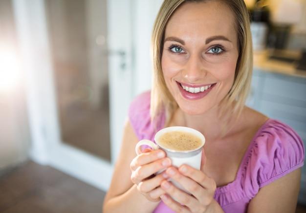 Jolie blonde femme prenant un café