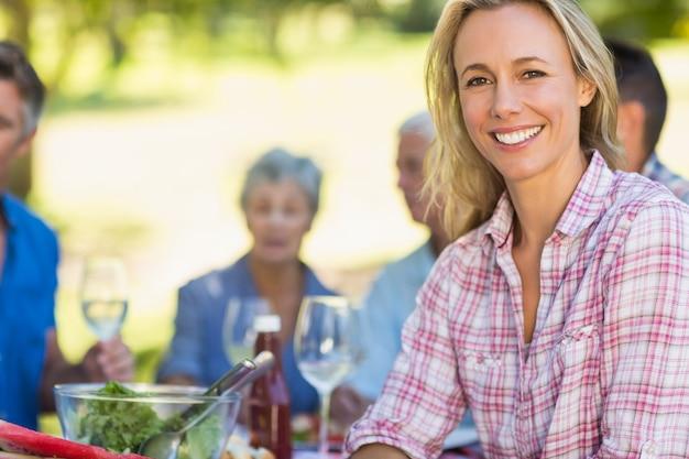 Jolie blonde femme souriant à la caméra pendant un pique-nique