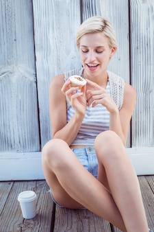 Jolie blonde femme tenant un cupcake