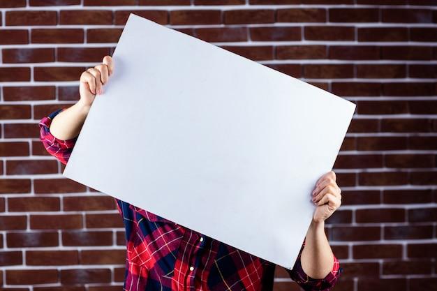 Jolie blonde femme tenant une pancarte blanche