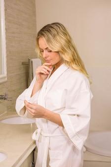 Jolie blonde femme tenant un test de grossesse dans la salle de bain