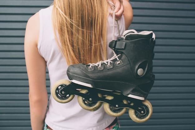 Jolie blonde fille posant avec des patins à roulettes à l'extérieur. portrait de mode de vie d'été