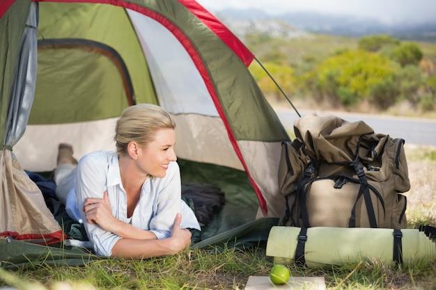 Jolie blonde heureuse se trouvant dans la tente