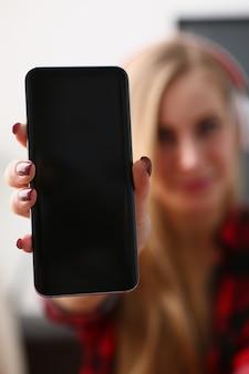 Jolie blonde jeune femme tenir un ordinateur portable dans les bras