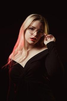 Jolie blonde à lunettes portant un chemisier aux épaules nues