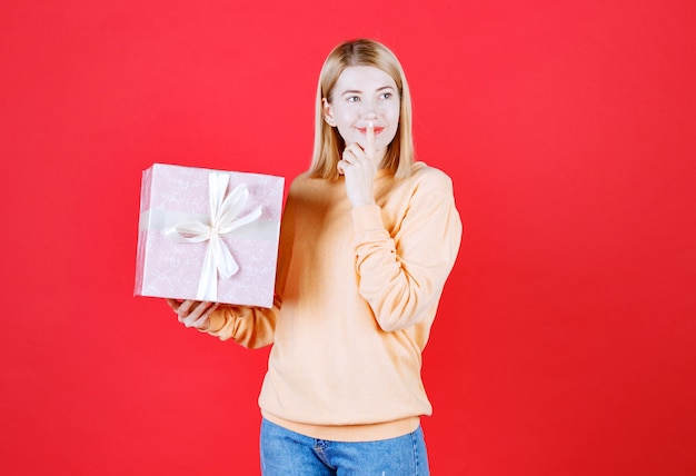 Jolie blonde met son doigt près de ses lèvres tout en tenant la boîte-cadeau devant le mur rouge