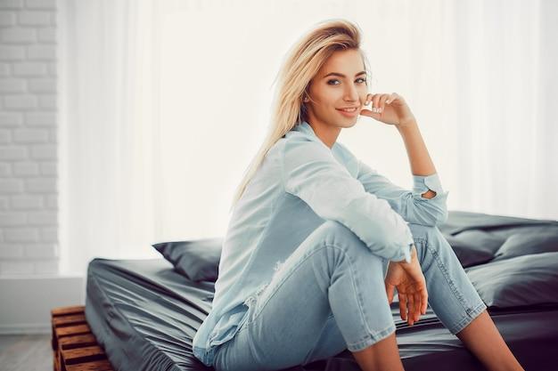 Jolie blonde naturelle assise sur le lit
