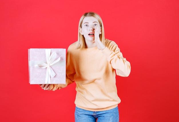 Jolie blonde tenant la boîte-cadeau tout en appelant quelqu'un devant le mur rouge