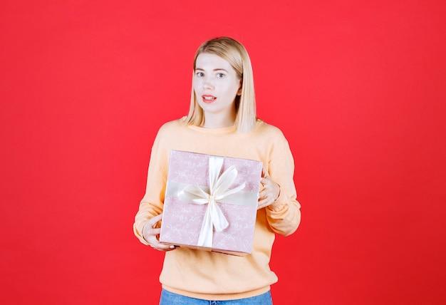 Jolie blonde tenant le coffret cadeau avec ses deux mains devant le mur rouge