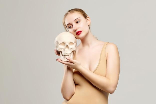 Jolie blonde tient un crâne dans ses mains. le concept de photographie convient au domaine de la cosmologie, de la médecine et des soins de santé.