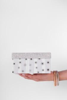 Jolie boîte-cadeau en argent tenue dans la main et espace de copie