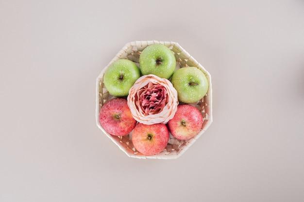 Jolie boîte avec des pommes sur blanc.