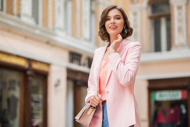 Jolie bonne femme loking walking street vêtue d'une veste rose d'humeur romantique