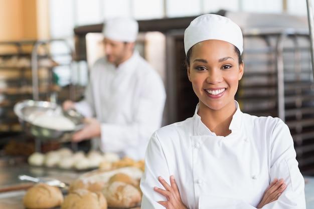 Jolie boulanger souriant à la caméra