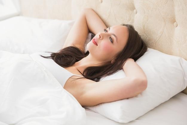 Jolie brune allongée dans son lit