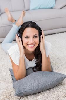 Jolie brune allongée sur le tapis en écoutant de la musique