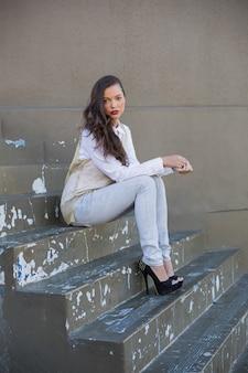Jolie brune assise dans les escaliers
