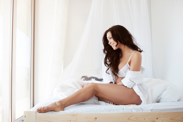 Jolie brune assise sur son lit