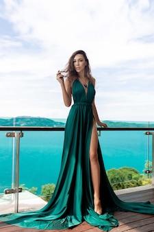 Jolie brune aux cheveux bouclés posant debout sur la terrasse