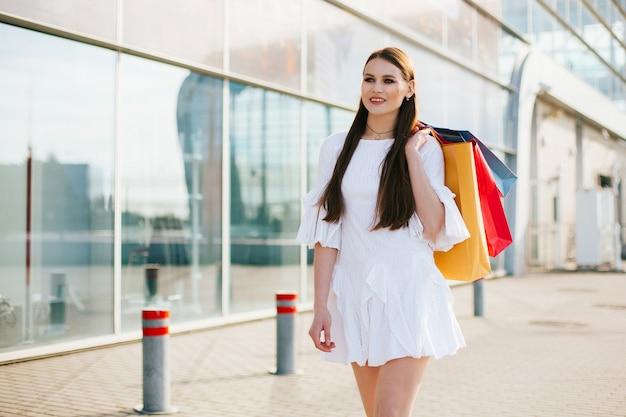 Jolie brune aux cheveux longs marchant avec des sacs à provisions devant un bâtiment moderne