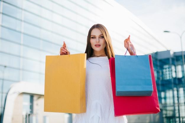 Jolie brune aux cheveux longs se tient avec des sacs à provisions devant un bâtiment de verre moderne