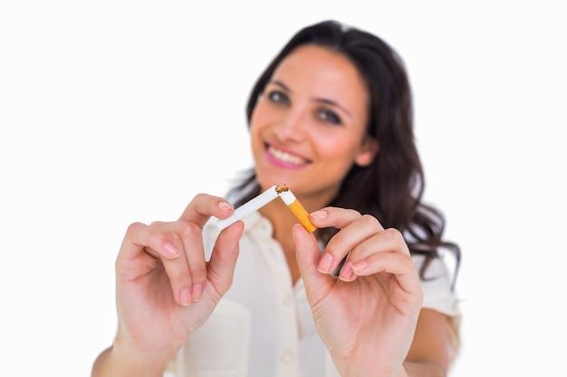Jolie brune brisant une cigarette